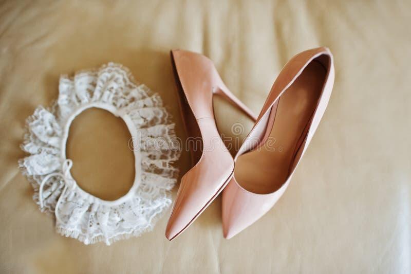 罗斯在高跟鞋的新娘鞋子有在皮革沙发的袜带的 免版税库存图片