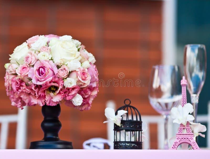 罗斯开花与小埃佛尔铁塔的花束在婚礼桌上 免版税库存照片
