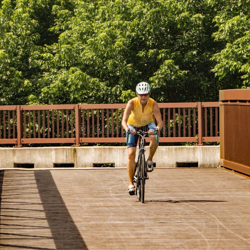罗阿诺克河林荫道路的女性骑自行车者 免版税库存照片