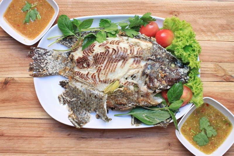 罗非鱼鱼烤与在白色盘的盐和有辣Sauc 免版税库存照片
