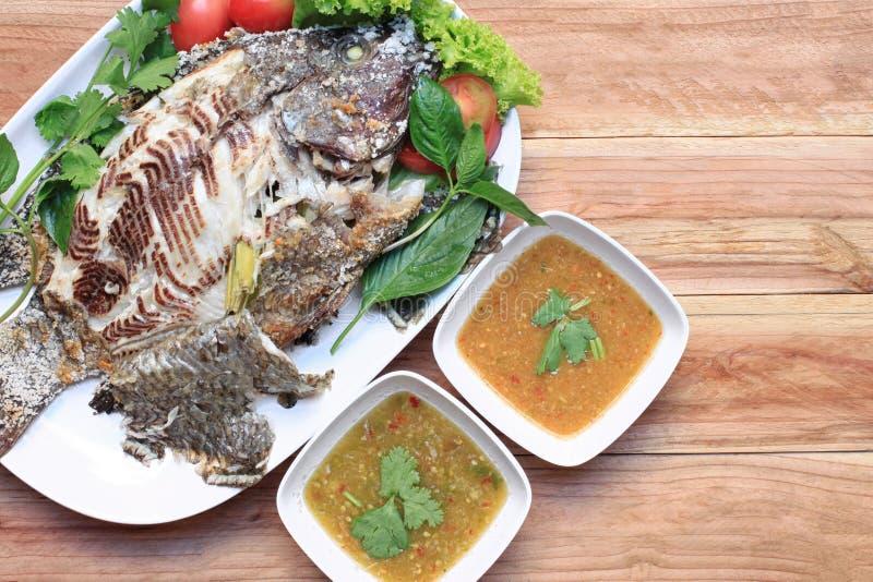 罗非鱼鱼烤与在白色盘的盐和有辣Sauc 图库摄影