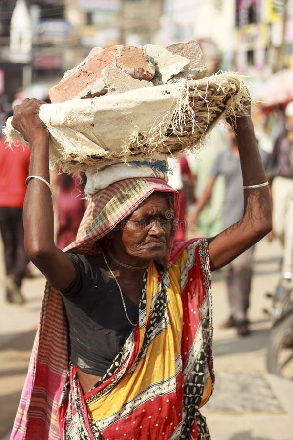 罗马妇女运载在他的头的砖 免版税库存图片