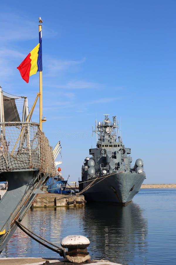 罗马尼亚军舰在口岸和罗马尼亚旗子停泊了 库存图片