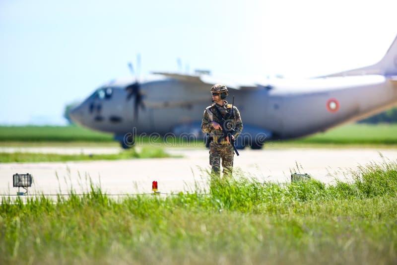 罗马尼亚陆军士兵与保加利亚空军一架Alenia C-27J斯巴达军用货机一起在一个军事空军基地巡逻 库存照片