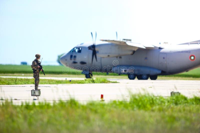 罗马尼亚陆军士兵与保加利亚空军一架Alenia C-27J斯巴达军用货机一起在一个军事空军基地巡逻 免版税库存图片
