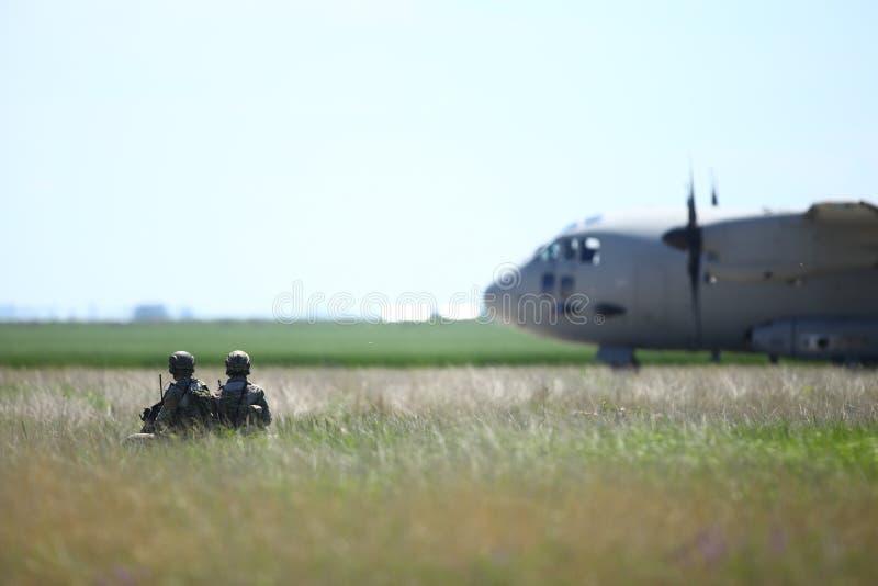 罗马尼亚陆军士兵在保加利亚空军的一个军事基地上巡逻,一架Alenia C-27J斯巴达军用货机从保加利亚空军起飞 库存照片