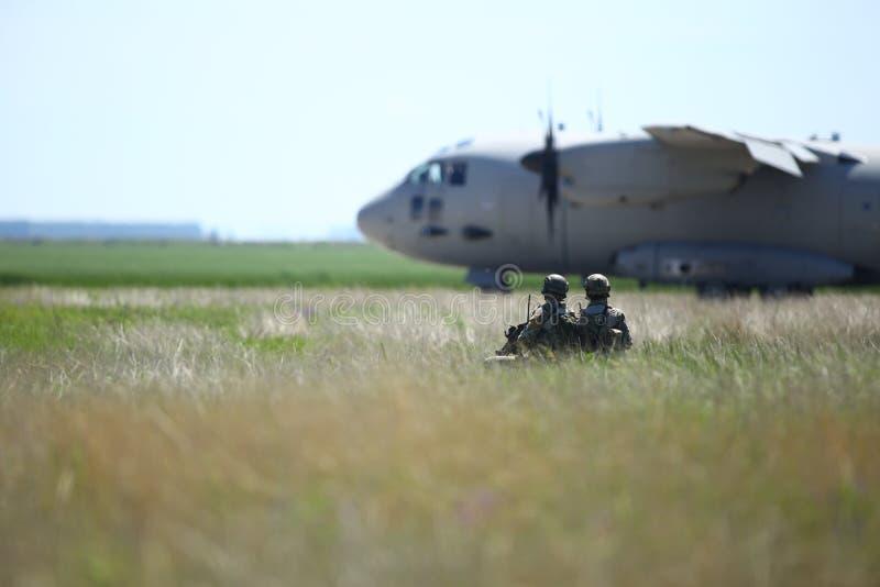 罗马尼亚陆军士兵在保加利亚空军的一个军事基地上巡逻,一架Alenia C-27J斯巴达军用货机从保加利亚空军起飞 库存图片