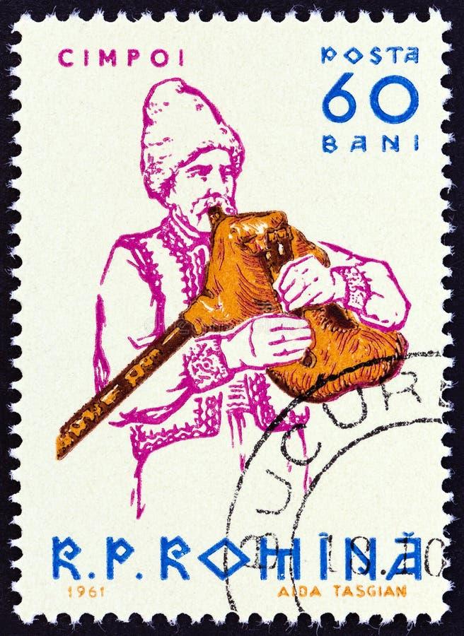 罗马尼亚-大约1961年:在罗马尼亚展示吹风笛者打印的邮票,大约1961年 库存图片