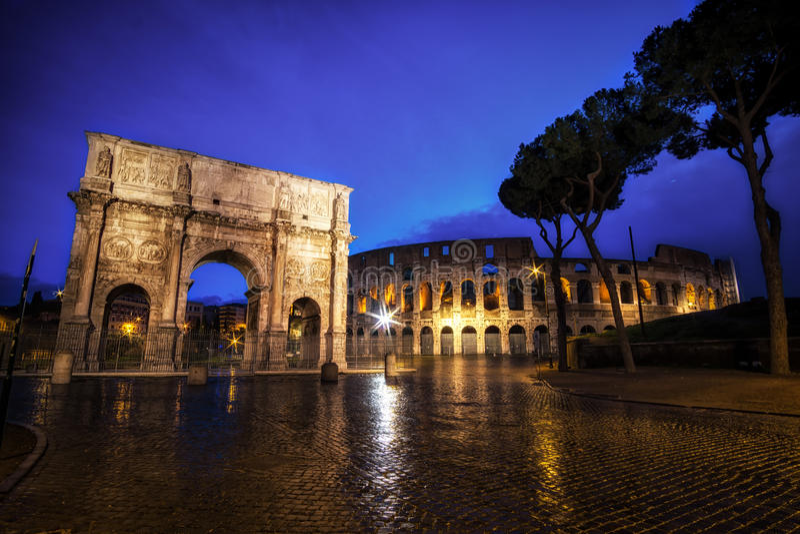 罗马斗兽场和康斯坦丁曲拱在晚上 免版税库存照片