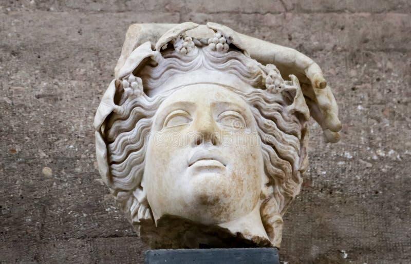 罗马雕象-从古老科林斯湾希腊的神的片段有花或葡萄的在波浪发和一部分的手 库存图片