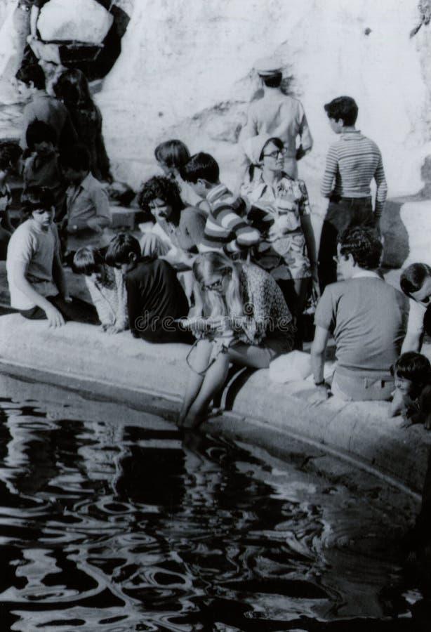 罗马,意大利,1970年-一个年轻,白肤金发的女性游人平静地读一本书,当刷新她的在Trevi喷泉时的脚 库存照片