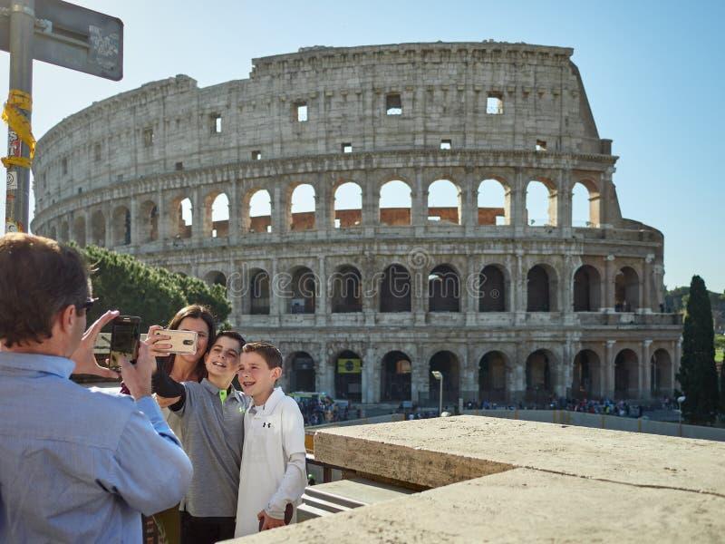 罗马,意大利, 2018年 家庭在一晴朗和温暖的天春天采取在罗马斗兽场前面的一selfie 图库摄影