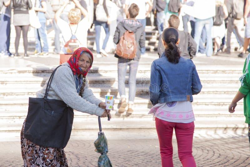 罗马,意大利,2011年10月9日:老妇人请求施舍在入口对一个天主教会 库存照片