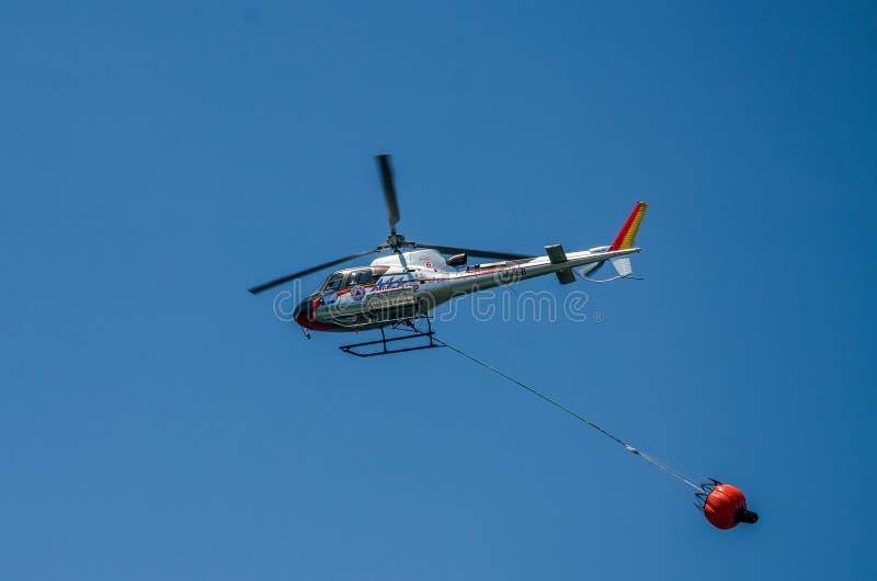 罗马,意大利- 2017年7月:消防队员直升机在救援活动时积在第勒尼安海和熄灭的水 免版税库存图片