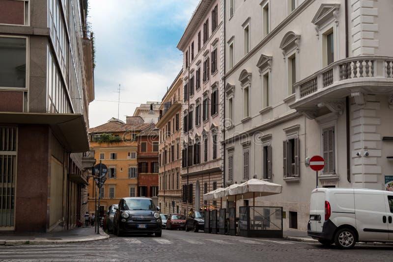 罗马,意大利- 2018年8月21日:典型的老罗马狭窄的街道 与伞的可爱的边路café 免版税库存照片