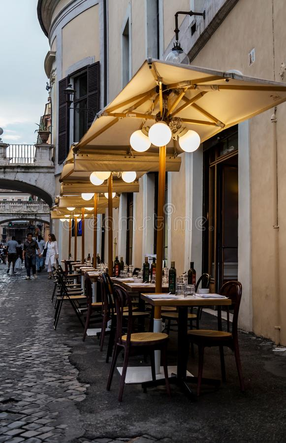 罗马,意大利- 2018年8月20日:典型的老罗马狭窄的街道 与空的桌、伞和灯笼的可爱的边路café 库存图片