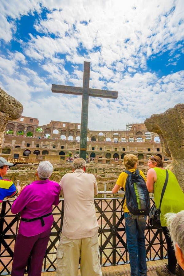 罗马,意大利- 2015年6月13日:在罗马大剧场里面,看一个大十字架的人们 从后面,好的颜色的照片 免版税库存照片