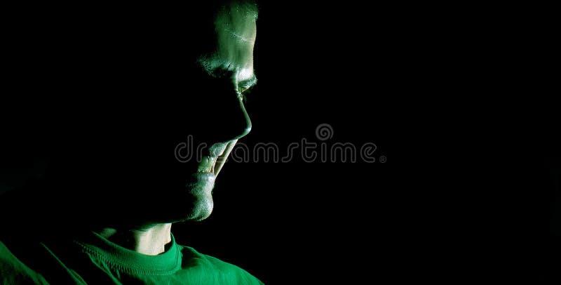罪恶低调画象,恶魔,坏,人的恼怒的面孔 一个人的恼怒的剪影有握紧的牙的在黑背景 库存图片