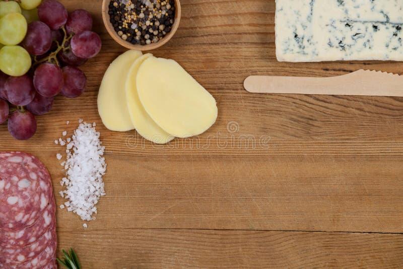 羊乳干酪乳酪、葡萄和火腿与各种各样的成份在砧板 免版税库存图片