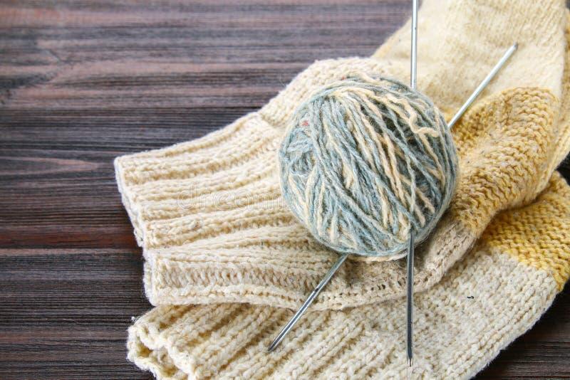 羊毛和在一张木桌上的被编织的袜子球与编织针的 刺绣用品 免版税库存照片