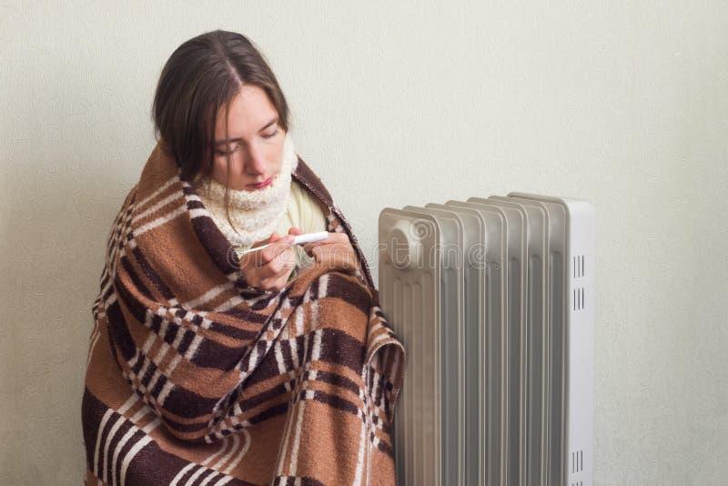 羊毛温暖的格子花呢披肩的年轻病的妇女在家检查她的温度的与温度计 免版税库存图片