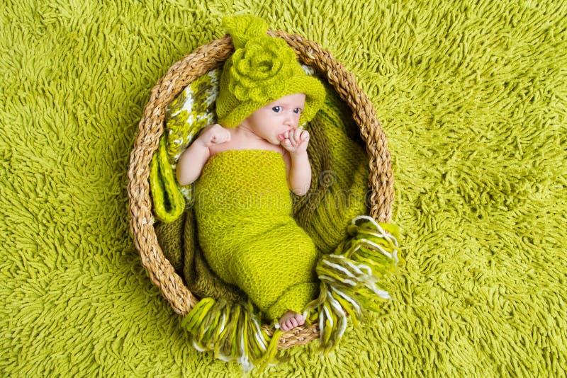 羊毛绿色帽子的新出生的婴孩在篮子里面 免版税图库摄影