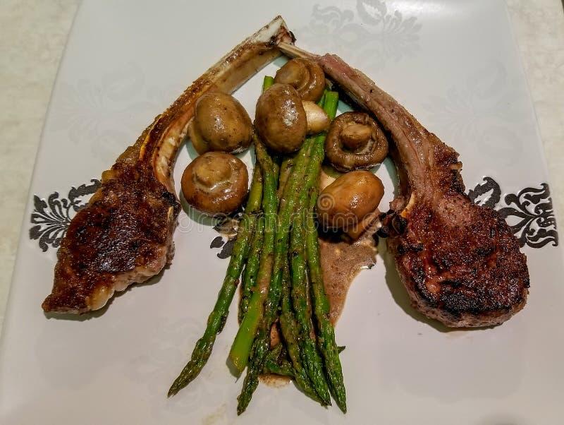 羊羔炸肉排用芦笋和蘑菇用调味汁,在一块白色陶瓷板材 免版税库存图片