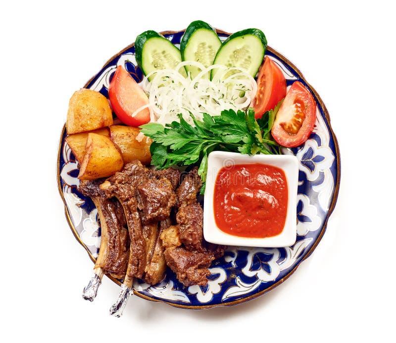 羊羔鲜美烤肋骨特写镜头在白色桌上的 食家烤排骨和油煎的土豆楔子的关闭在白色板材机智 图库摄影