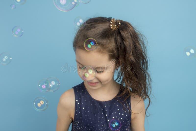 美丽使用与泡影的矮小的个长发女孩在一个更加亲切的操场 免版税库存图片
