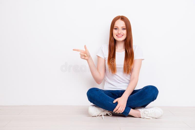 美丽全长身体尺寸的照片她她的夫人坐地板腿横渡了手臂间的食指表明空的空间 库存图片