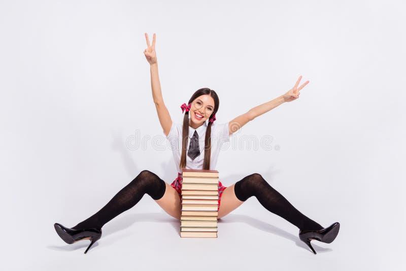 美丽全长身体尺寸的照片她她的老师在开放腿臀部尾巴v标志假期之间坐地板书堆 免版税库存图片