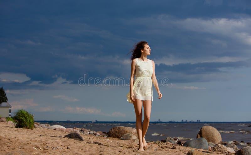 美丽减肥走在海滩的赤足女孩反对海 库存照片