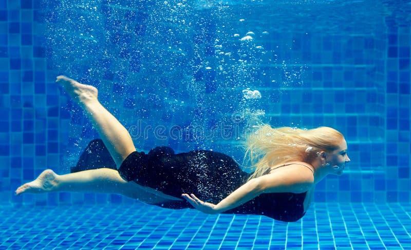 美丽加上大小在水池的妇女潜水 免版税库存图片