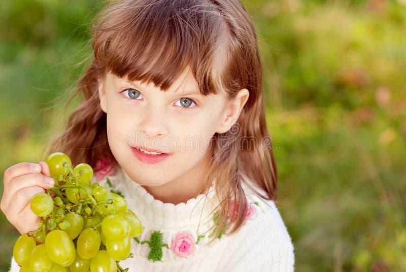 美丽吃女孩小葡萄的绿色 库存图片