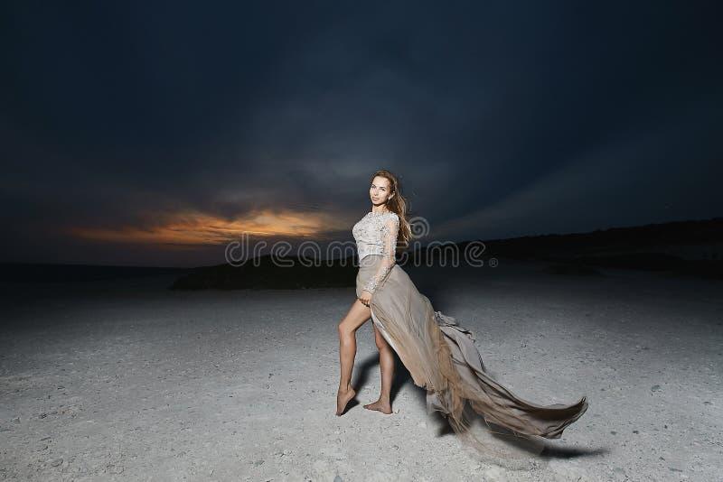 美丽和年轻深色的式样妇女,米黄鞋带礼服的,摆在日落 免版税库存照片