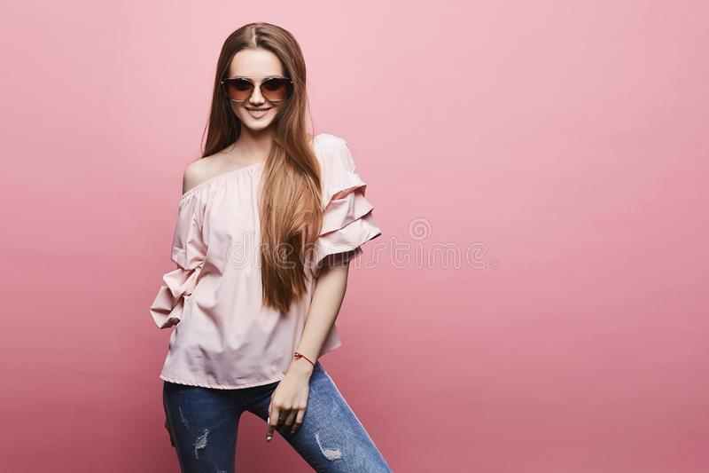 美丽和性感的式样白肤金发的女孩有赤裸肩膀的一件女衬衫的和时兴的桃红色太阳镜的,摆在  库存照片