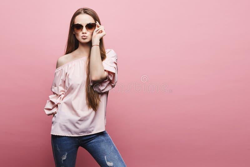 美丽和性感的式样白肤金发的女孩有赤裸肩膀的一件女衬衫的和送空气的时兴的桃红色太阳镜的 库存图片