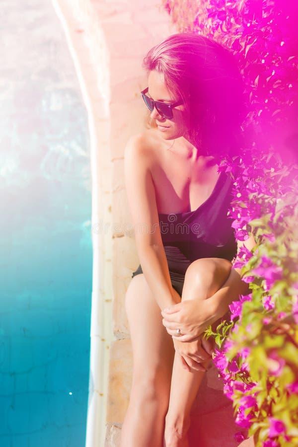 美丽和性感的由水池的妇女佩带的太阳镜,得到好晒黑 免版税图库摄影