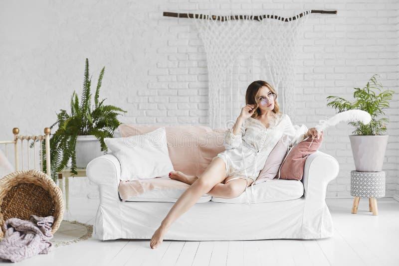 美丽和性感的长腿的白肤金发的式样女孩时兴的玻璃的和时髦的缎睡衣的坐白色 免版税库存照片