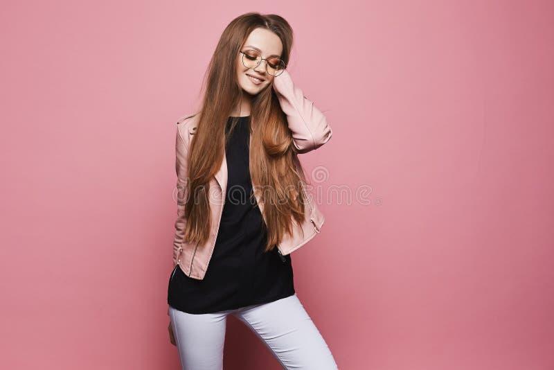 美丽和愉快的白肤金发的式样女孩有明亮的构成的和戴时兴的眼镜在皮夹克和在黑色 库存照片