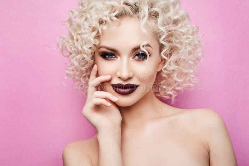 美丽和时兴的式样女孩有使的蓝眼睛惊奇,有卷曲金发的和有专业明亮的构成的,微笑  库存照片