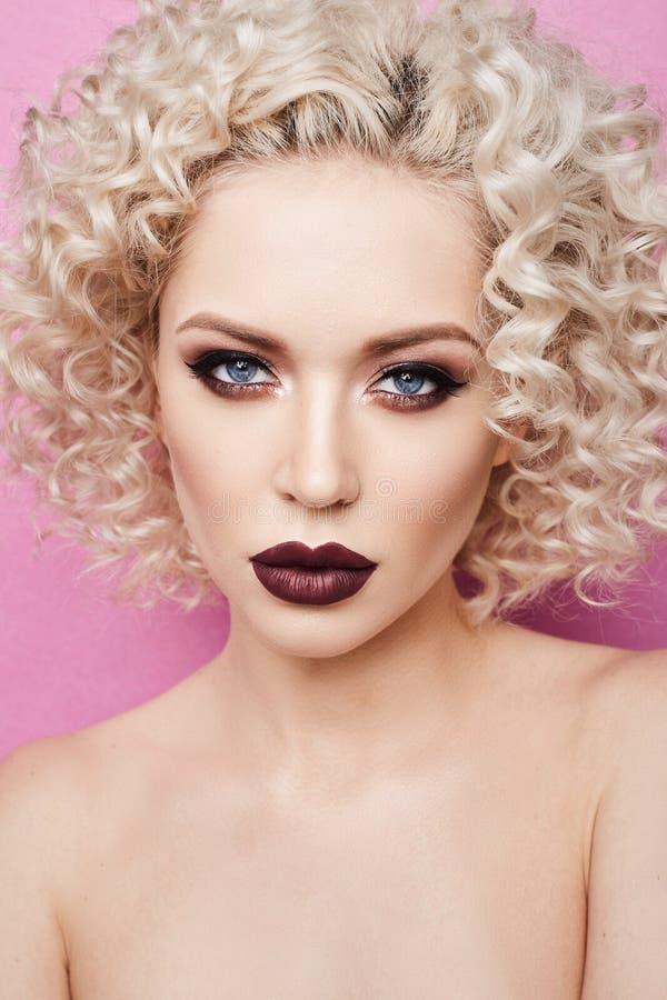 美丽和时兴的式样女孩有使的蓝眼睛惊奇,有卷曲金发的和有专业明亮的构成的 库存图片