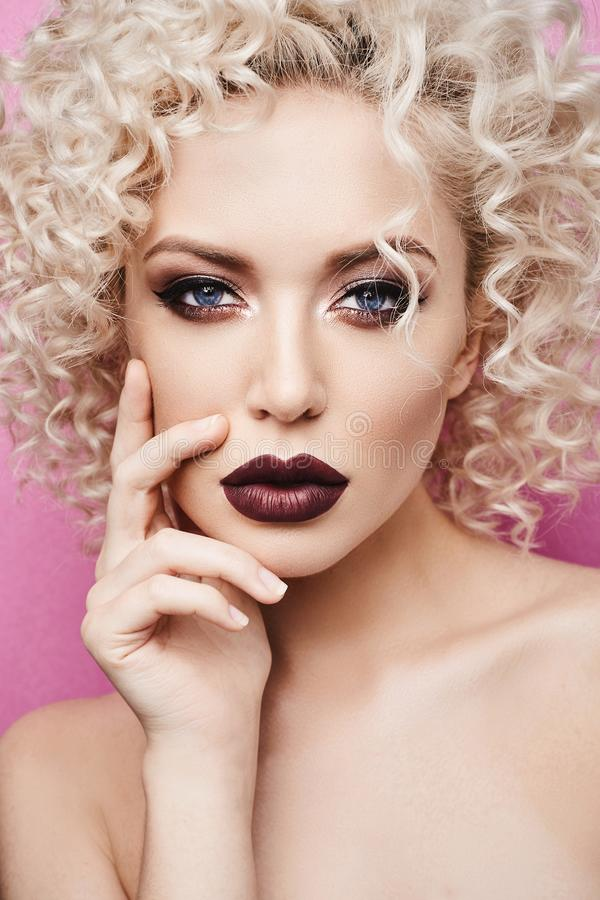美丽和时兴的式样女孩有惊人的蓝眼睛的,有卷曲金发的和有深红嘴唇的被隔绝在 免版税库存图片