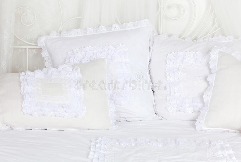美丽和白色软绵绵地系带了在床上的枕头。 库存图片
