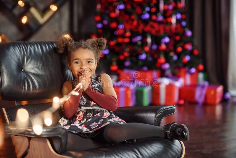 美丽坐在圣诞树的扶手椅子的孩子女孩5-6岁佩带的时髦的礼服在屋子里 r r 免版税库存图片