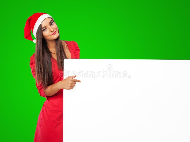 美丽女孩iin圣诞老人的帮手帽子拿着大白板 免版税图库摄影