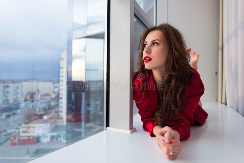 美丽女性获得放松的乐趣看窗口,画象 库存图片