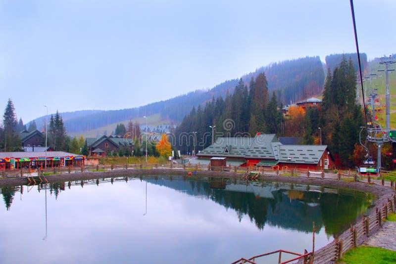 美丽如画的湖和旅游房子乌克兰滑雪的Bukovel 与山湖的风景在度假村 免版税库存照片