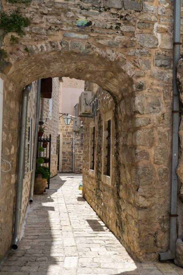 美丽如画的狭窄的街道在布德瓦,黑山老镇  古老房子 在堡垒里面的石曲拱 库存图片