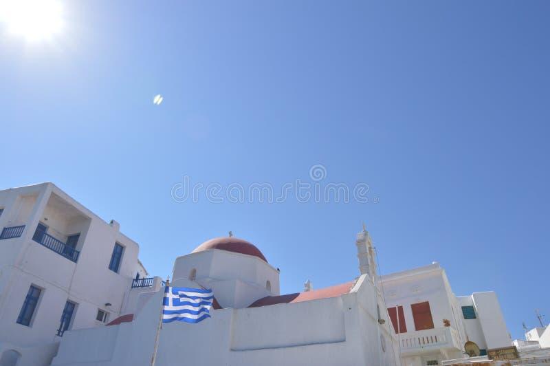 美丽如画的红色屋顶和希腊的旗子在米科诺斯岛逃出克隆岛的Chora  建筑学使旅行巡航环境美化 免版税库存图片
